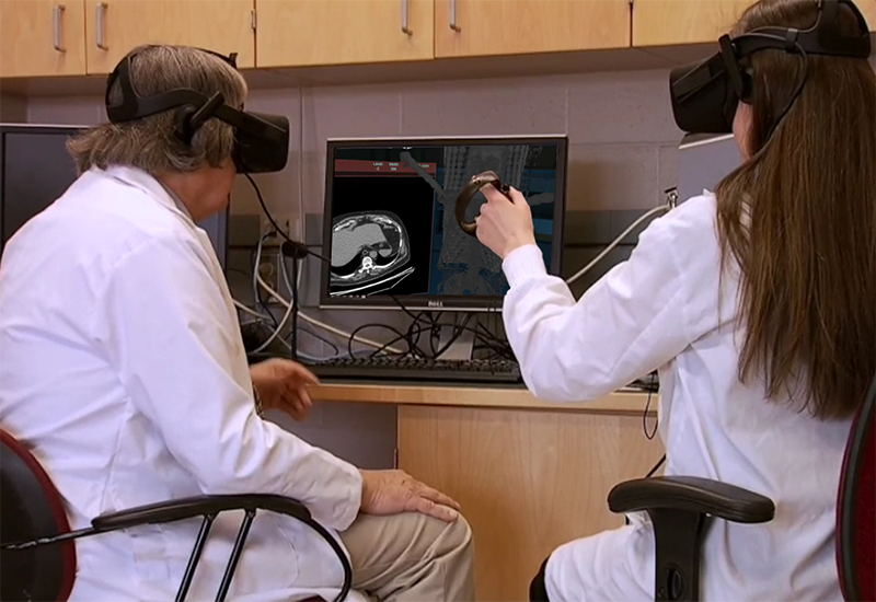 Man and woman in labcoats looking at computer monitor while wearing VR headsets