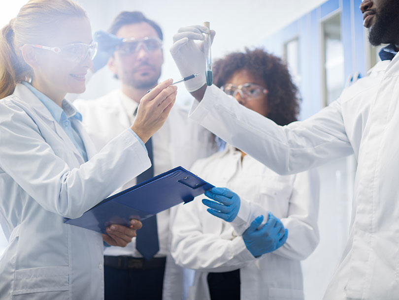 People in scrubs looking at test tube